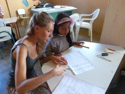 A young Ecuadorian student gets help from a Teaching volunteer.