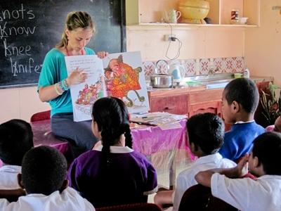 Teaching volunteer reads a story to a class in a school in Fiji