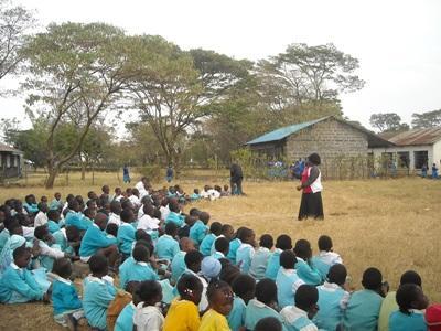 A female teacher teaches a class of elementary school children in Kenya, Africa