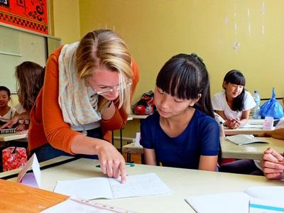 A child at a school in Mongolia gets some help from a Teaching volunteer.