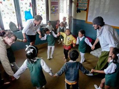 Three volunteers conduct a class for a group of Nepalese school children