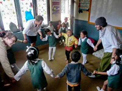 三名義工在課堂帶領一群尼泊爾學童去學習