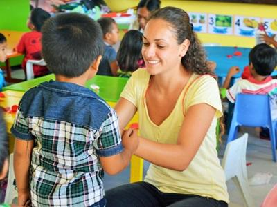 A student at a Filipino school gets help from a female volunteer teacher
