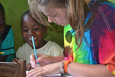 Projects Abroad volunteer on a Winter Break Trip to Ghana helps a local child at a school.