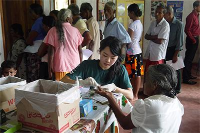 Projects Abroad volunteers performs a basic health check-up at an outreach at the Medicine Winter Break Trip in Sri Lanka.