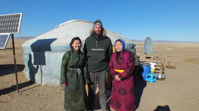 Male volunteer poses with his nomad host family in Mongolia during his volunteer trip