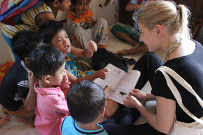 A female volunteer reads with children as volunteer work overseas in Cambodia